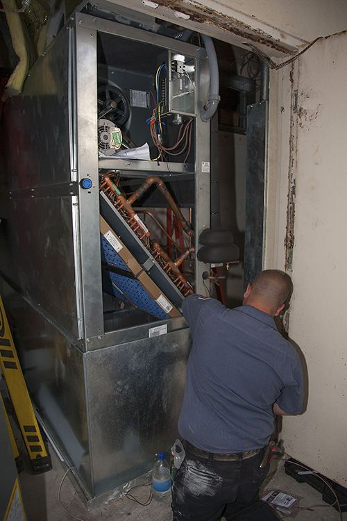 Sean McCutcheon's service technician repairing an air conditioning unit.